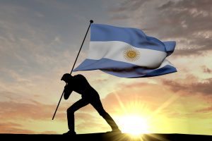 Argentina flag being pushed into the ground by a male silhouette. 3D Rendering