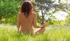 Nudista meditando en naturaleza