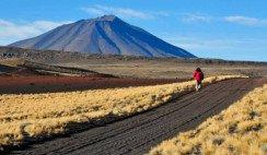 mujer caminando cerca de volcán en La Payunia