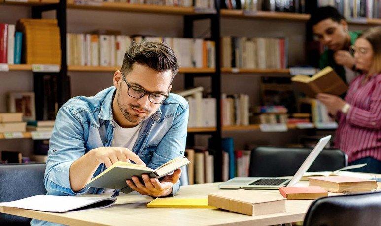 joven leyendo un libro en biblioteca
